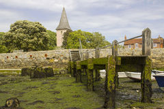 A small wooden jetty covered with barnacles and seaweed in the harbour at Bosham village in West sussex in the South of England Royalty Free Stock Photo