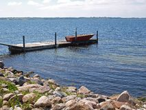 Small wooden jetty dock with a dingy Royalty Free Stock Image