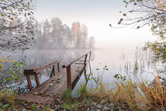Small wooden pier in autumn foggy morning. Small wooden pier on still lake in autumn foggy morning royalty free stock photo