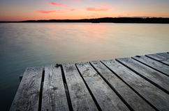 Small wooden pier on big lake at sunset Stock Images