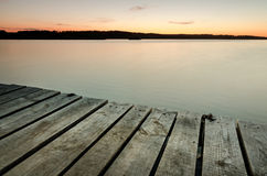 Small wooden pier on big lake at sunset Stock Photo