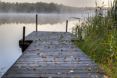 Small wooden pier on a lake. Early morning. Mist drifts above the lake in the background. Leafs have fallen onto the wooden pier stock image