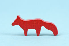Small wooden red fox toy on blue background Royalty Free Stock Photos