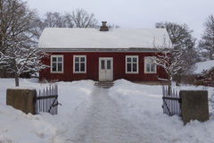 Small wooden red house covered by snow Stock Photography