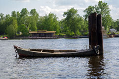 Small wooden rowboat, fishing boat on the river piers Royalty Free Stock Images