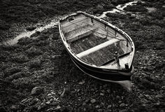 Small wooden rowboat moored at low tide Stock Image