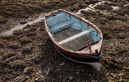 Small wooden rowboat moored at low tide Stock Photography
