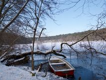 Small wooden rowboat in a snowy lake in winter. Small wooden rowboat in a frozen lake in winter with leafless deciduous tree branches and a snowy mountainous Stock Photo