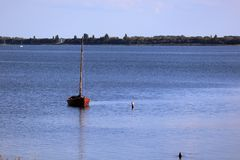 Small, wooden sailboat anchoring in Baltic Sea, no people royalty free stock photo