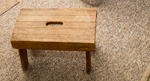 Small wooden step stool. Small four legged wooden step stool on carpet Stock Image