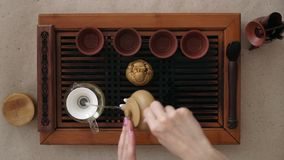 On a small wooden table are all the necessary tools for the tea ceremony. The girl gently pours tea from a teapot.  stock video footage