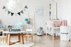 Small table in child room. Small wooden table standing on a white carpet in a child room interior Royalty Free Stock Photo