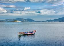 Small wooden traditional fishing boat against new gas factory, P Stock Photos