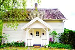 Small Wooden White House with Front Porch, Nordic Homes. Beautiful scandinavian white small house with a nice front porch and a colorful garden, Norway Royalty Free Stock Photography