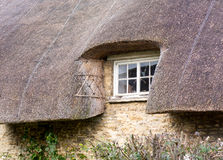 Small wooden window under thatched roof Royalty Free Stock Photo
