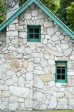 Small wooden windows and chimney stack in a stone cottage with green trim and gable royalty free stock photos