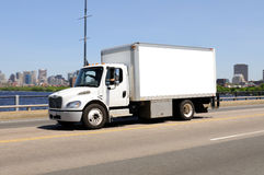 Small Work Truck in. Small work truck on the highway. Clean white panel, side view, clipping path. City of Boston in background Royalty Free Stock Photo