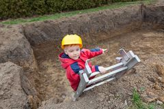 Small worker helped your father. Little boy with a spade helps parents during the construction of the pool stock photos