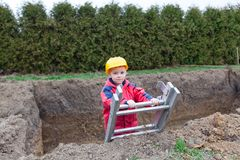 Small worker helped your father. Little boy with a spade helps parents during the construction of the pool stock image