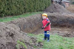 Small worker helped your father. Little boy with a spade helps parents during the construction of the pool stock images