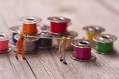 Small workers prepares the material for sewing. Tailoring concep Stock Images