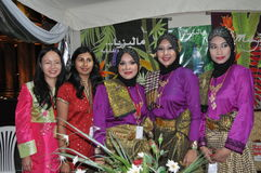 Small World Malaysian Women. Small World held in Abu Dhabi at 2010, Malaysian women with colorful shirts and dressing in red and viola colors and sympathy face Stock Image