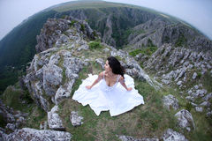Small world woman. Young woman in white dress sitting on mountain top looking Stock Photography