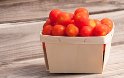 Small woven basket with ripe cherry tomatoes Royalty Free Stock Images