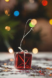 Small wrapped gift box and snowflake scattered on wooden table Royalty Free Stock Photos