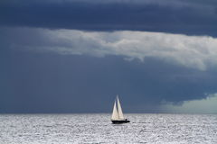 Small yacht on big ocean and dark clouds Royalty Free Stock Photos