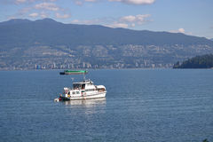 Small Yacht on English Bay. A small, private yacht is anchored in English Bay with North Vancouver and Stanley Park in the background Stock Image