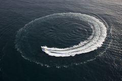 Small yacht making a circle in the water Royalty Free Stock Photos