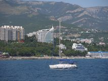A small yacht sailing along the blue sea near the shore strewn with stones and town houses standing among the. Picturesque nature. . For your design Royalty Free Stock Images