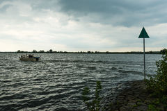 Small yacht in stormy weather on a Dutch river Royalty Free Stock Photography
