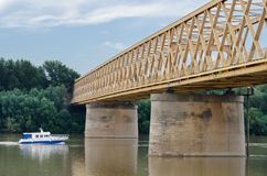Small yacht traveling on river under bridge in summer Stock Photos