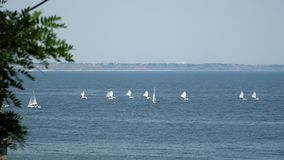 Small yacht under sail floating in the sea On the horizon is visible city stock video
