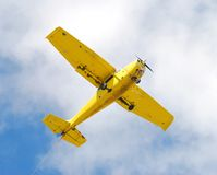 Small yellow airplane. Small private airplane passing overhead stock image