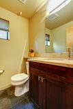 Small yellow bathroom with wood. Royalty Free Stock Images