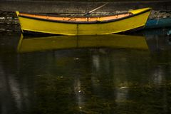 Small yellow boat reflected in the turbid water of the lagoon. royalty free stock photography