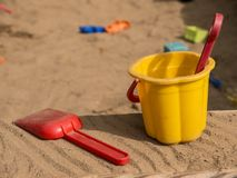 Bucket, puddle and rake in kid`s sandbox side view. Small yellow bucket and red puddle with red rake in kid`s sandbox side view royalty free stock photography