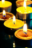 Small yellow burning candle. In the dark Stock Photo