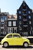 Small yellow CAR. CAR little yellow against the black building in Amsterdam Royalty Free Stock Images