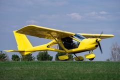 Small yellow charter airplane waiting on a green field to take off.  royalty free stock photo