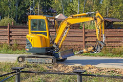 Small yellow crawler excavator for screwing piles. On road Royalty Free Stock Image