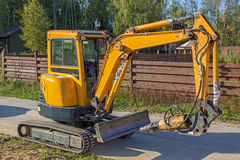 Small yellow crawler excavator for screwing piles Royalty Free Stock Images