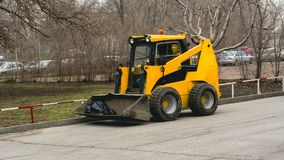 Small yellow excavator removes garbage. In the city Stock Photography
