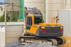 Small yellow excavator working at the construction site. Mini ba. Ckhoe shoveling sand and gravel Royalty Free Stock Photo