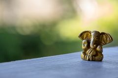 Small yellow Ganesha figure with unfocused background. Beautiful golden Ganesh statue with open palm. Asian religion concept. Small yellow Ganesha figure with royalty free stock photography