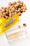 Small yellow grater with a bunch of hazelnuts Royalty Free Stock Photos