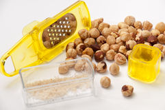 Small yellow grater with a bunch of hazelnuts Royalty Free Stock Photography